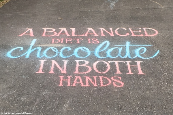 Chalk drawing in driveway saying A balanced diet is chocolate in both hands.