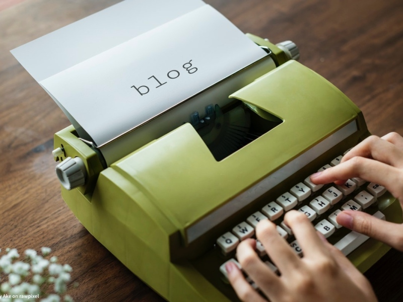 person typing the word blog on green vintage typewriter